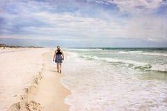 漫步在晴朗的海滩艺术性的照片的成熟妇女 库存图片