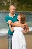 漫步由海的孕妇和她的丈夫。 免版税图库摄影
