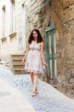 漫步通过狭窄的街道的女孩 免版税库存图片