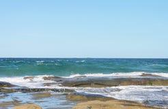 漫过完全成功古老熔岩流的海起泡沫和跑在参差不齐的岩石,与在天际的两艘船出口 免版税库存图片