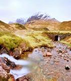漫过花岗岩石头的清楚的小河小河水 在重的云彩的斯诺伊山 库存图片