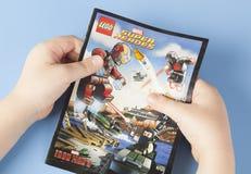 漫画书乐高特级英雄在儿童的手上 免版税库存照片