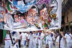 潘普洛纳,西班牙- 7月8 :有横幅的人步行沿着向下str的 免版税库存照片