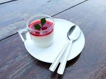 潘纳陶砖用在上面和两把匙子的草莓调味汁 免版税库存照片
