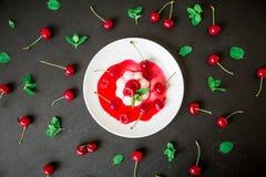 潘纳陶砖用在白色板材的樱桃糖浆在黑暗的背景和莓果,传统意大利点心 平的位置 顶视图 库存照片