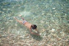 潜水在与石头的海水下的水下的风镜的小男孩在手 免版税库存照片