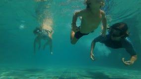 潜水在游泳场的幸福家庭的慢动作水下的射击 健康生活方式,活跃父母 股票录像