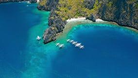 潜水的小船鸟瞰图在秘密盐水湖附近的在Miniloc海岛上 ElNido,巴拉旺岛 r 异常的石灰石岩石 影视素材