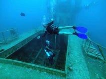 潜水者检查一艘被充斥的船 免版税库存照片