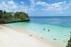 潜航在一个偏僻的热带海滩的清楚的绿松石水,冲绳岛,日本中的人们 库存照片