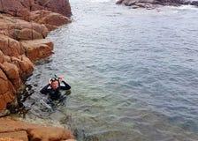 潜航在一个潮汐岩石水池的妇女 免版税库存图片