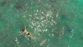 潜航在公海观看的珊瑚和异乎寻常的鱼的年轻女人的空中射击 股票录像