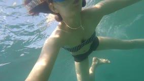 潜航在海或与游泳面具的海蓝色水中的少妇水下的selfie,不用水肺晴天 影视素材