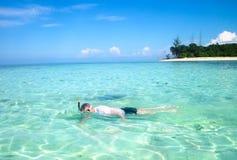 潜航在热带海岛旁边的年轻人 免版税库存图片