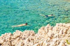 潜航在透明的岩石亚得里亚海的夫妇 库存照片