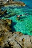 潜航通过绿松石水的比基尼泳装的俏丽的妇女在克罗地亚的海岸 免版税库存照片