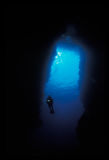 轻潜水员游泳的剪影在洞的 免版税库存图片