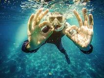 轻潜水员水下的陈列ok信号用两只手 免版税图库摄影