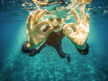 轻潜水员水下的陈列ok信号用两只手 图库摄影