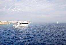 潜水员临近消遣红色礁石海运游艇 库存图片