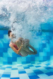 潜水在水面下在游泳池的女孩 库存照片