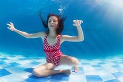 潜水在水面下在游泳池的女孩 免版税库存照片