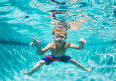 潜水在水面下在游泳池的年轻男孩 免版税图库摄影