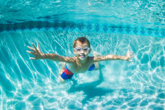 潜水在水面下在游泳池的年轻男孩 免版税库存照片