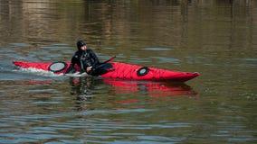 潜水服的一个人乘皮船做一次突然行动 图库摄影