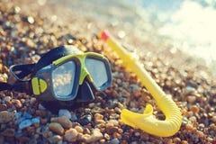 潜水概念-黑面具和废气管在Pebble海滩 免版税库存图片