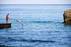 潜水从码头的两个男孩在海 库存照片