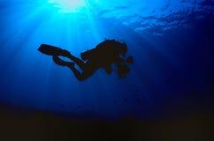 潜水者的剪影,当进入下来深蓝色时 库存图片