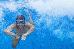 潜水面具的年轻人游泳在水池,达的爬泳 免版税库存照片