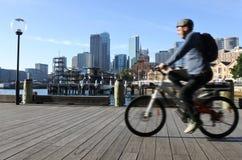 澳大利亚人乘驾沿悉尼环形码头悉尼Ne的一辆自行车 免版税库存图片