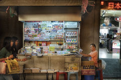 澳门, PEOPLE'S中华民国- 2012年10月18日:在小径的Newsstand's生活方式在晚上 库存照片