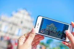 澳门- 2018年1月15日:有为照相的智能手机的手 免版税库存照片