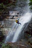 澳洲: rapelling蓝色山里人的瀑布 库存图片