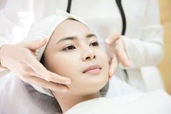 激光机器 得到激光治疗的少妇 应用关心皮肤透明油漆 得到面部秀丽治疗的少妇,取消染色 图库摄影