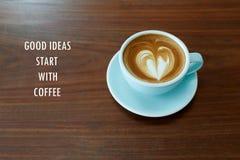 激动人心的正面行情`好想法开始以咖啡`用心脏形状拿铁咖啡和木书桌背景 库存图片
