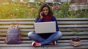 激动女性沟通与手机的男朋友,学习在长凳 免版税图库摄影