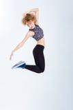 年轻激动妇女跳跃 库存照片