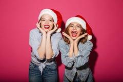 激动微笑戴圣诞节圣诞老人帽子的两个妇女朋友 免版税库存图片