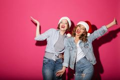 激动微笑戴圣诞节圣诞老人帽子的两个妇女朋友 库存照片