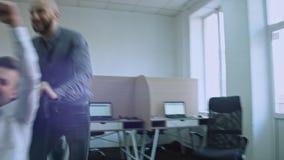 激动的不同的雇员获得乐趣一起在办公室,乘坐在椅子在工作,享受断裂,庆祝公司 股票视频