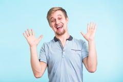 激动的人在幸福,姿态有效地惊叹了,表达的伟大的surprisement,在蓝色背景 库存图片