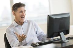 激动的使用台式计算机的商人呼喊的白色 图库摄影