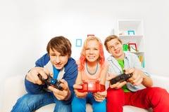 激动的十几岁拿着控制杆和戏剧比赛控制台 库存照片