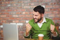 激动的商人紧握拳头在办公室 免版税库存图片