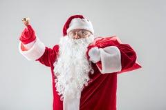 激动的圣诞老人敲响的响铃在度假 免版税库存照片