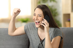 激动的在电话的妇女听的新闻 库存照片